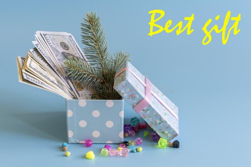 Caja de regalo con los dólares y una rama de un árbol de navidad El mejor regalo de la inscripción imagen de archivo