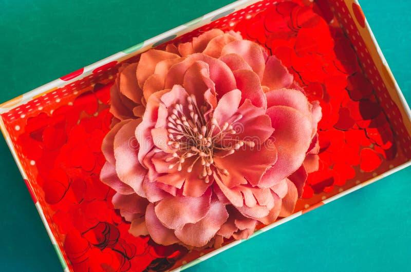 Caja de regalo con los pequeños corazones rojos y pasador de la flor en fondo azulverde imagen de archivo