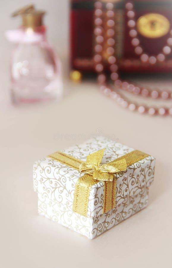Caja de regalo con motivos y un arco amarillo sobre un fondo decorativo foto de archivo libre de regalías