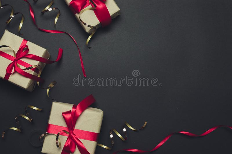Caja de regalo con un arco rojo de la cinta con brillo y decoraciones de oro Endecha plana, visi?n superior, espacio de la copia foto de archivo