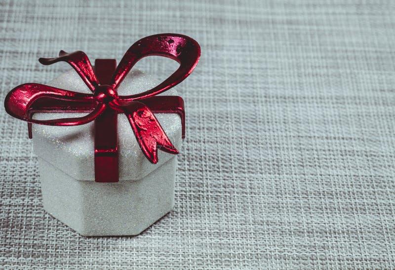 Caja de regalo con una cinta roja en un fondo gris imágenes de archivo libres de regalías