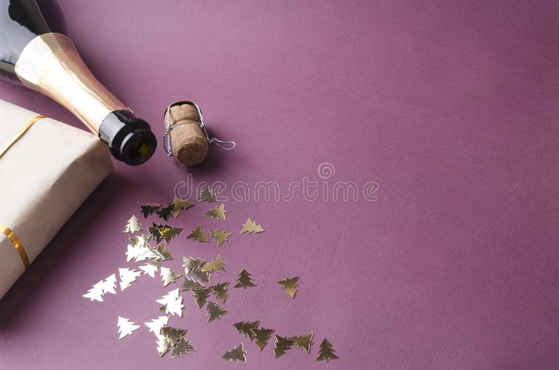 Caja de regalo, confeti, botella abierta de champán en el fondo púrpura Espacio vac?o para el texto imagen de archivo libre de regalías