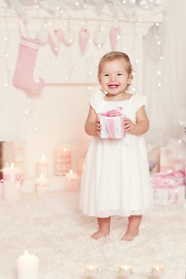 Caja de regalo de apertura del niño de la Navidad actual, muchacha del niño que celebra Navidad imagen de archivo libre de regalías