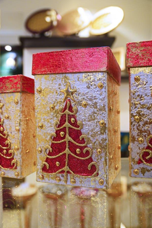 Caja de regalo de la Navidad adornada con el árbol de navidad rojo con brillo del oro imagen de archivo