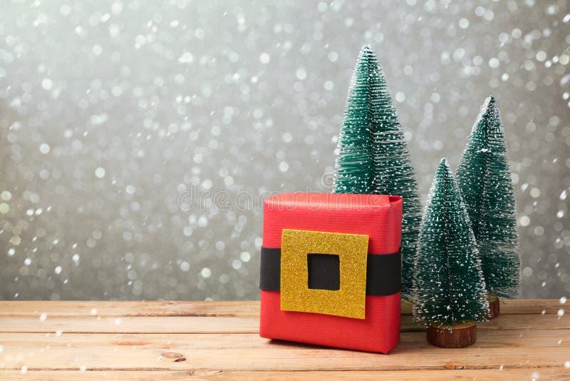 Caja de regalo de la Navidad con el embalaje creativo hecho en casa en la tabla de madera sobre fondo del bokeh fotografía de archivo