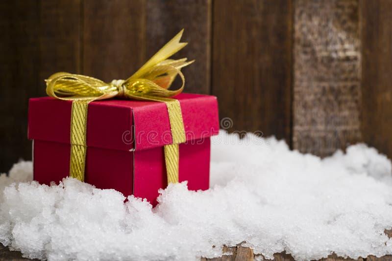 Caja de regalo de la Navidad con un arco de la cinta del oro en nieve foto de archivo