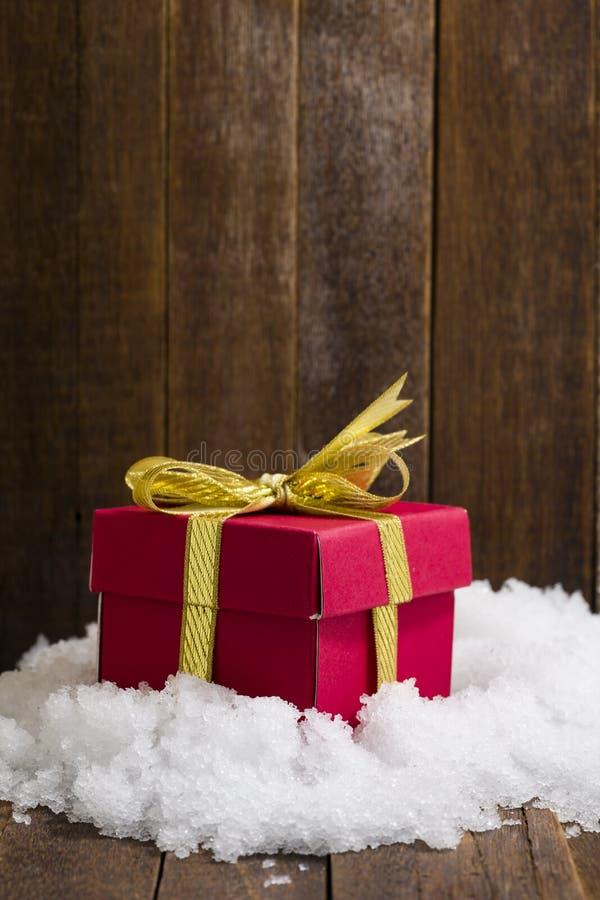 Caja de regalo de la Navidad con un arco de la cinta del oro en nieve fotografía de archivo libre de regalías