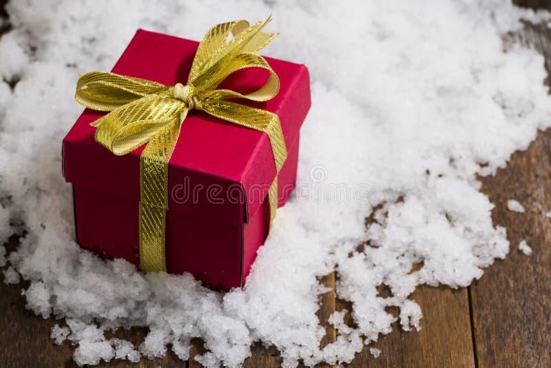 Caja de regalo de la Navidad con un arco de la cinta del oro en nieve foto de archivo libre de regalías