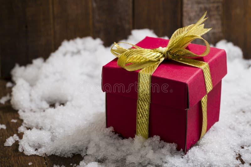 Caja de regalo de la Navidad con un arco de la cinta del oro en nieve fotografía de archivo