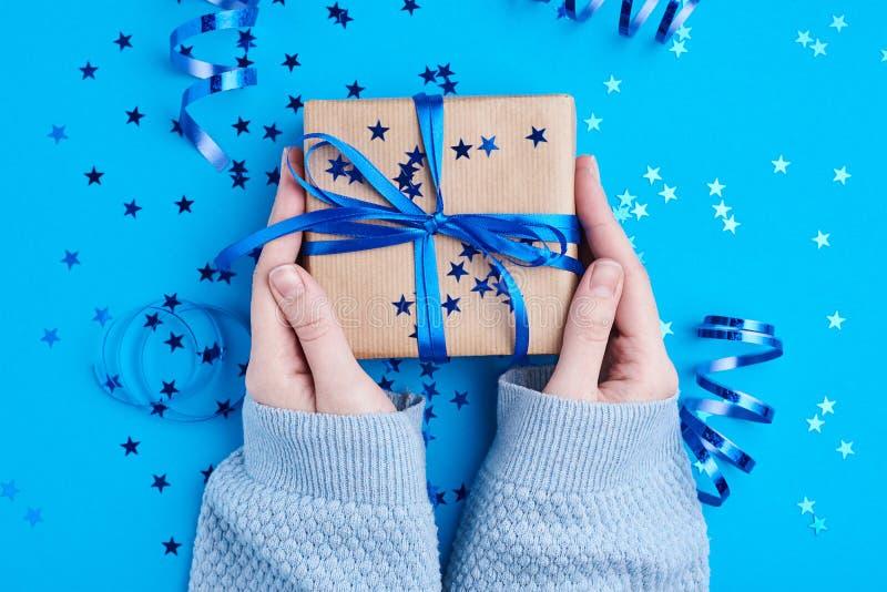 Caja de regalo del control de la mano de la mujer envuelta en el papel de Kraft imagen de archivo