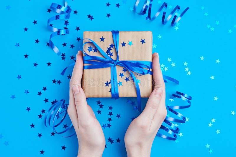 Caja de regalo del control de la mano de la mujer envuelta en el papel de Kraft fotos de archivo libres de regalías