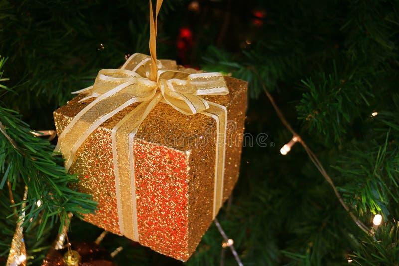 Caja de regalo del cuadrado del brillo del oro con el ornamento de la Navidad del arco de la cinta del oro en el árbol de navidad imagen de archivo