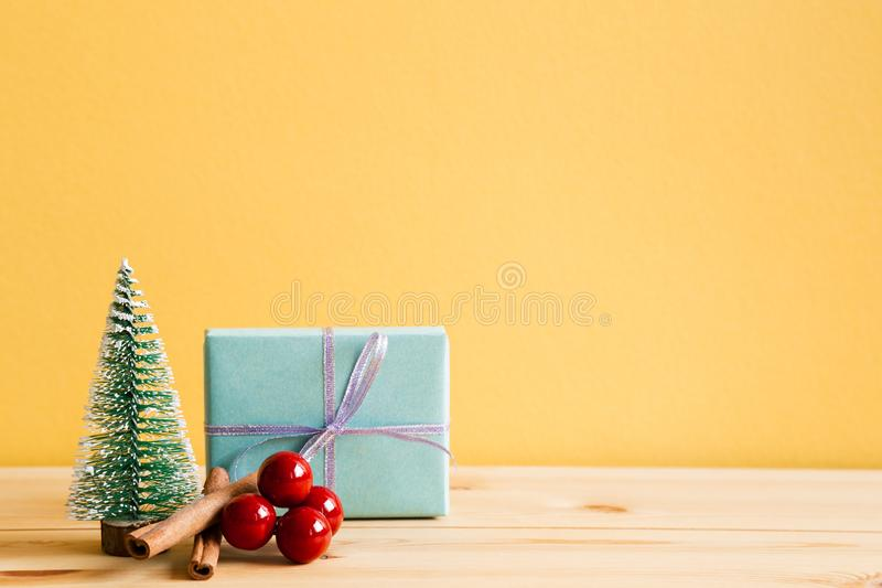 Caja de regalo del ornamento de la Navidad, árbol de pino, bayas rojas en la tabla de madera imágenes de archivo libres de regalías