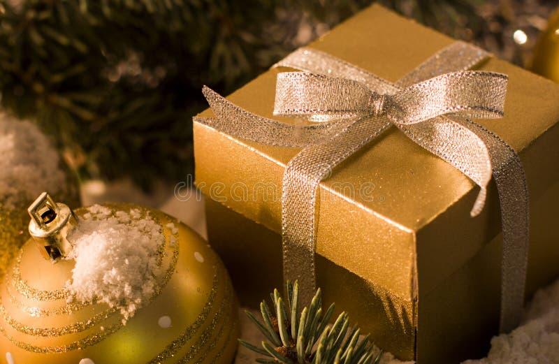 Caja de regalo del oro con el arco de plata, bolas del juguete fotos de archivo libres de regalías