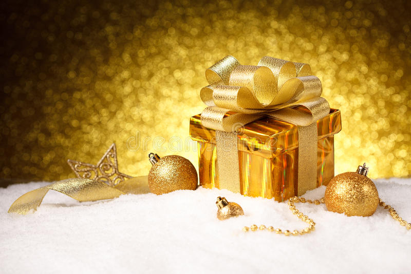 Caja de regalo del oro de la Navidad con las bolas y decoración en nieve fotos de archivo libres de regalías