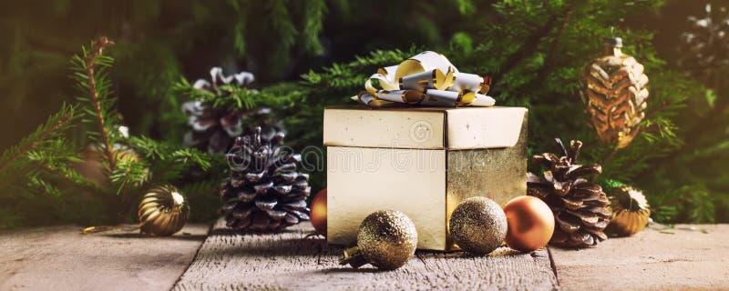 Caja de regalo del oro de la Navidad o del Año Nuevo, con las decoraciones festivas foto de archivo