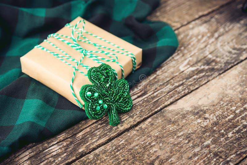 Caja de regalo elegante con la broche verde de la cuerda y del trébol, en fondo rústico de madera imagen de archivo libre de regalías