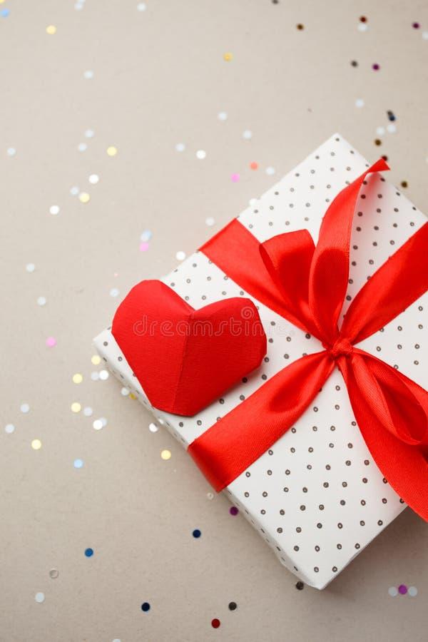 Caja de regalo en fondo gris con el corazón y el confeti Sorprenda su amado El concepto del día de tarjeta del día de San Valentí foto de archivo