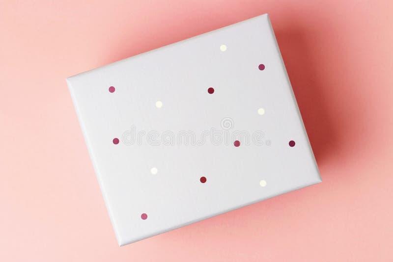 Caja de regalo en un primer rosado del fondo, visi?n superior foto de archivo