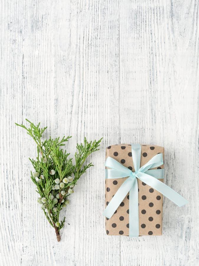Caja de regalo envuelta en documento marrón y ramita sobre el fondo de madera blanco foto de archivo