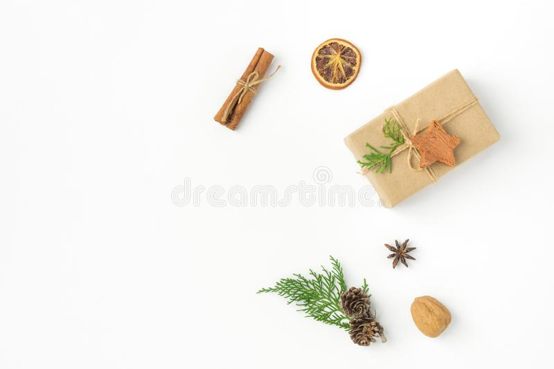 Caja de regalo envuelta en el papel del arte atado con el fondo nuts del blanco del canela del enebro de los conos del pino de la fotos de archivo libres de regalías