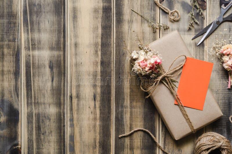 Caja de regalo envuelta en papel del arte hecho a mano hermoso de DIY con la tarjeta anaranjada del espacio en blanco en fondo de foto de archivo libre de regalías