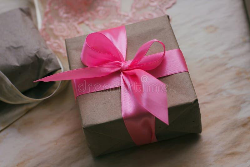 Caja de regalo envuelta en papel marrón del arte y atada por la cinta de satén rosada Proceso de empaquetado Tienda de regalos De fotos de archivo