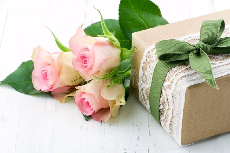 Caja de regalo envuelta en papel marrón, el cordón blanco y un arco verde imagenes de archivo