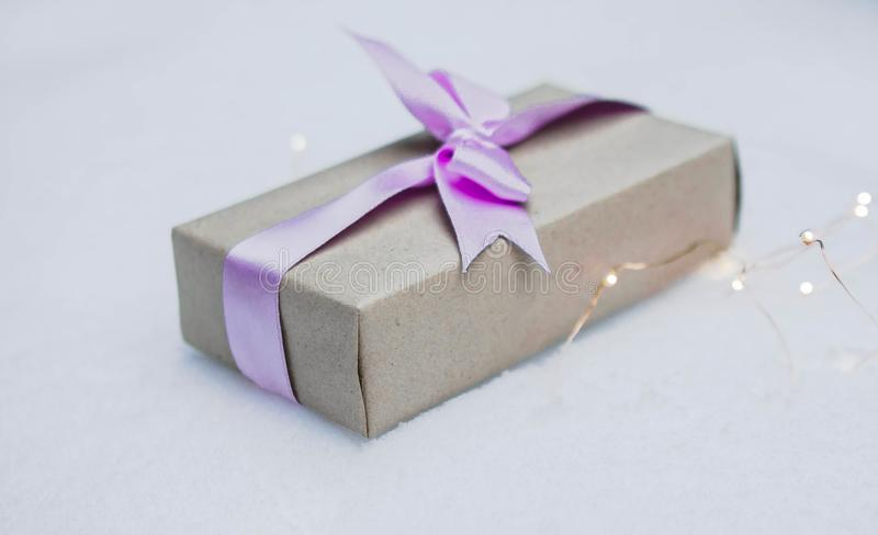 Caja de regalo envuelta en papel reciclado marrón con un arco púrpura imagen de archivo