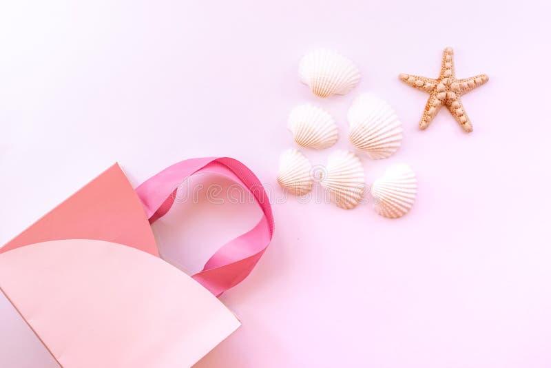 Caja de regalo, estrellas de mar y conchas marinas en un fondo rosado delicado El concepto de un regalo para el verano fotos de archivo