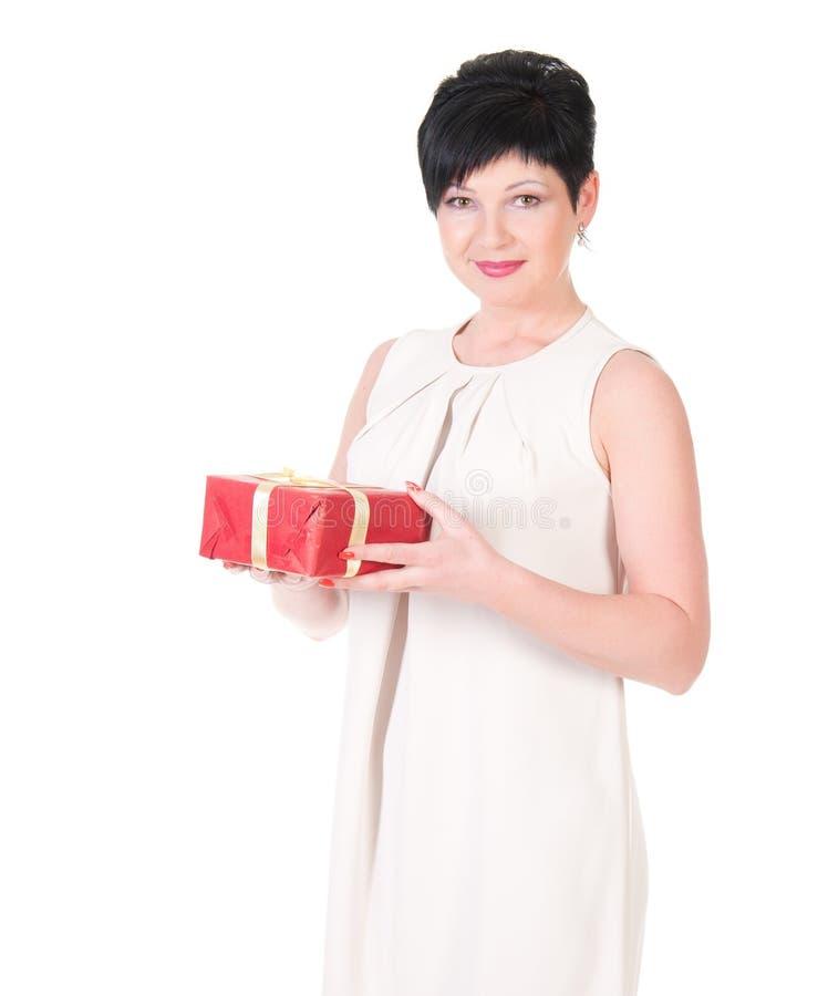 Caja de regalo feliz del asimiento de la sonrisa de la mujer de negocios en manos. foto de archivo libre de regalías