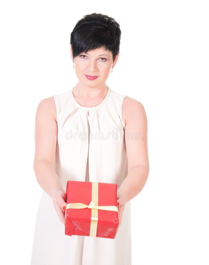 Caja de regalo feliz del control de la sonrisa de la mujer de negocios en manos. fotos de archivo
