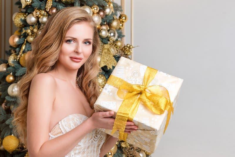 Caja de regalo feliz de la abertura de la mujer Blonde de lujo con el regalo de la Navidad Tema de la celebración de la Feliz Nav imagen de archivo libre de regalías