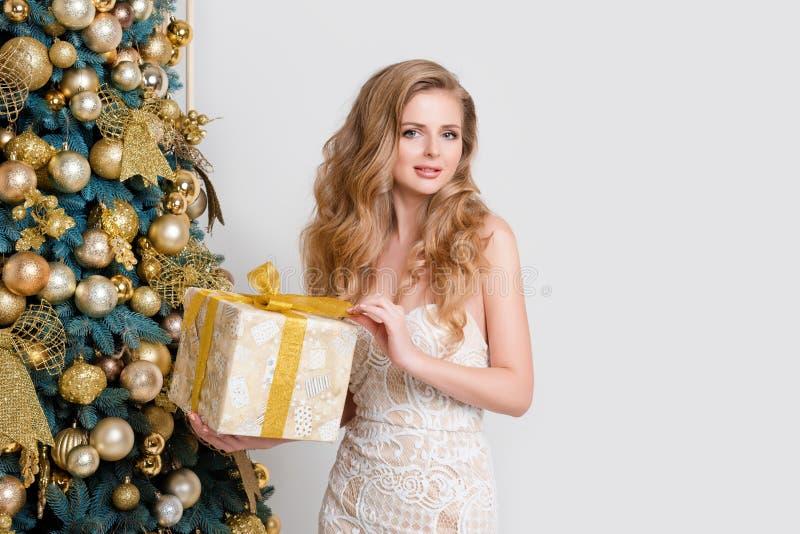 Caja de regalo feliz de la abertura de la mujer Blonde de lujo con el regalo de la Navidad Tema de la celebración de la Feliz Nav fotografía de archivo libre de regalías