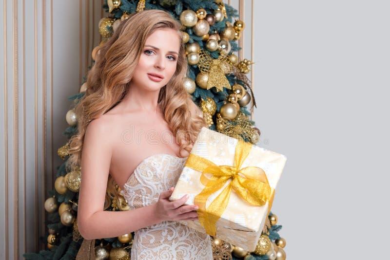 Caja de regalo feliz de la abertura de la mujer Blonde de lujo con el regalo de la Navidad Tema de la celebración de la Feliz Nav imágenes de archivo libres de regalías