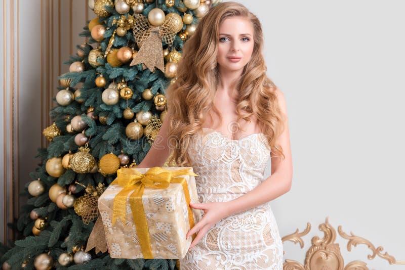 Caja de regalo feliz de la abertura de la mujer Blonde de lujo con el regalo de la Navidad Tema de la celebración de la Feliz Nav imagen de archivo