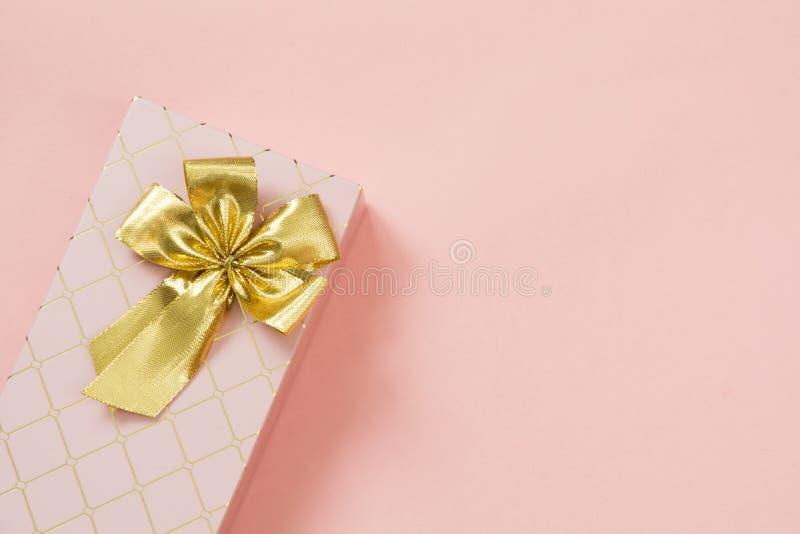 Caja de regalo femenina con la cinta de oro en rosa en colores pastel dinámico Cumpleaños Copie el espacio foto de archivo libre de regalías