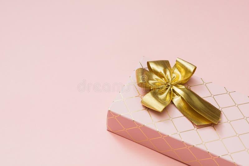 Caja de regalo femenina con la cinta de oro en rosa en colores pastel dinámico Cumpleaños Copie el espacio fotografía de archivo libre de regalías
