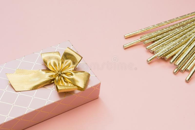 Caja de regalo femenina con los accesorios de oro de la cinta y del cóctel en rosa en colores pastel dinámico Copie el espacio fotos de archivo libres de regalías
