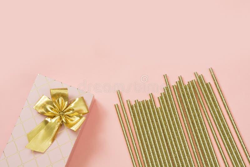 Caja de regalo femenina con los accesorios de oro de la cinta y del cóctel en rosa en colores pastel dinámico Copie el espacio imagen de archivo