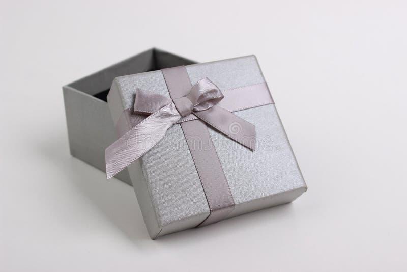 Caja de regalo gris con un arco fotografía de archivo