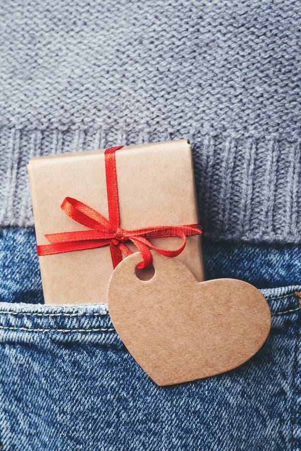 Caja de regalo de Kraft con el arco y la etiqueta rojos foto de archivo