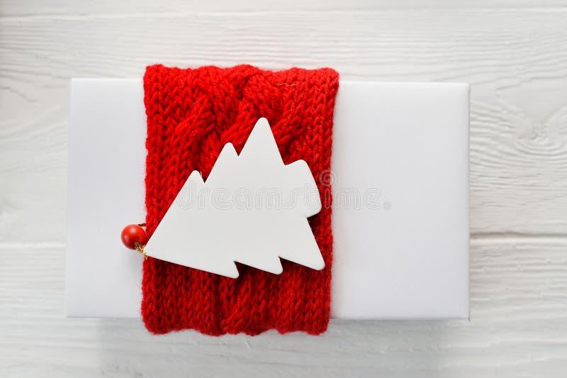 Caja de regalo de la Navidad blanca con la etiqueta hecha punto roja de la cinta y de la maqueta en la forma de árbol de abeto en imágenes de archivo libres de regalías