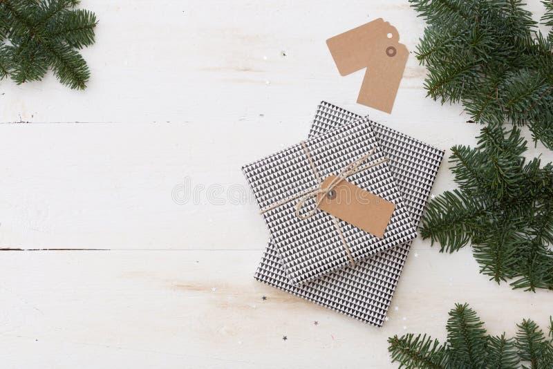 Caja de regalo de la Navidad con la etiqueta Presente del Año Nuevo en caja blanco y negro con las ramas del abeto en la tabla de fotos de archivo libres de regalías