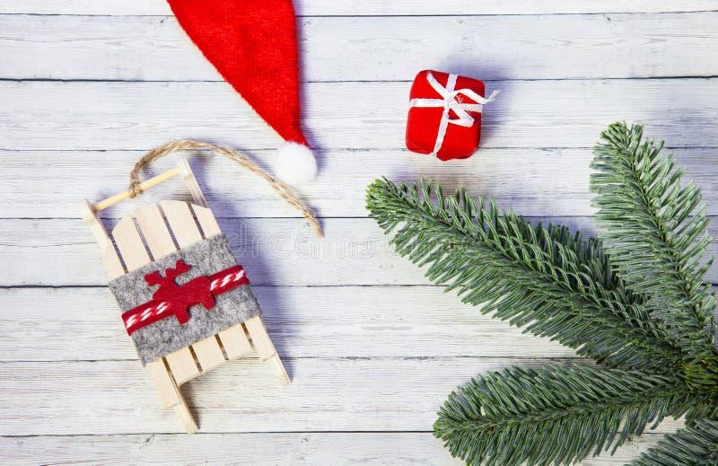 Caja de regalo de la Navidad, el trineo de Papá Noel y ramas del abeto en un fondo de madera, visión superior foto de archivo libre de regalías
