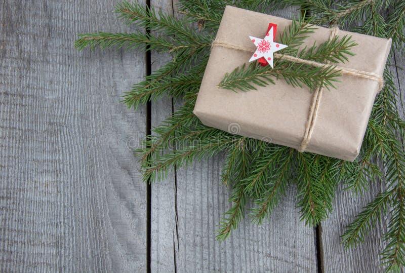 Caja de regalo de la Navidad en la tabla de madera, artesanía que envuelve, pergamino, guita, ramitas del árbol de abeto, actual  fotos de archivo libres de regalías