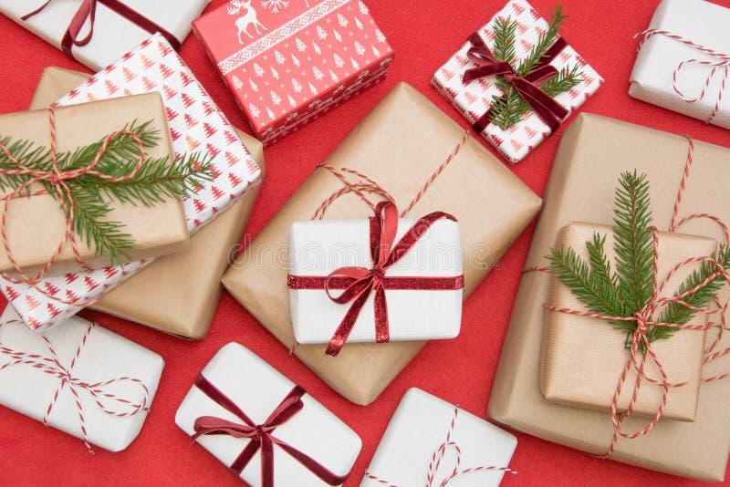 Caja de regalo de la Navidad envuelta en documento del ornamento y cinta decorativa de la cuerda roja sobre superficie roja Afici fotografía de archivo