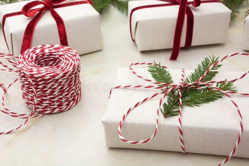 Caja de regalo de la Navidad envuelta en el documento blanco del arte y la cinta decorativa de la cuerda roja sobre superficie ma foto de archivo