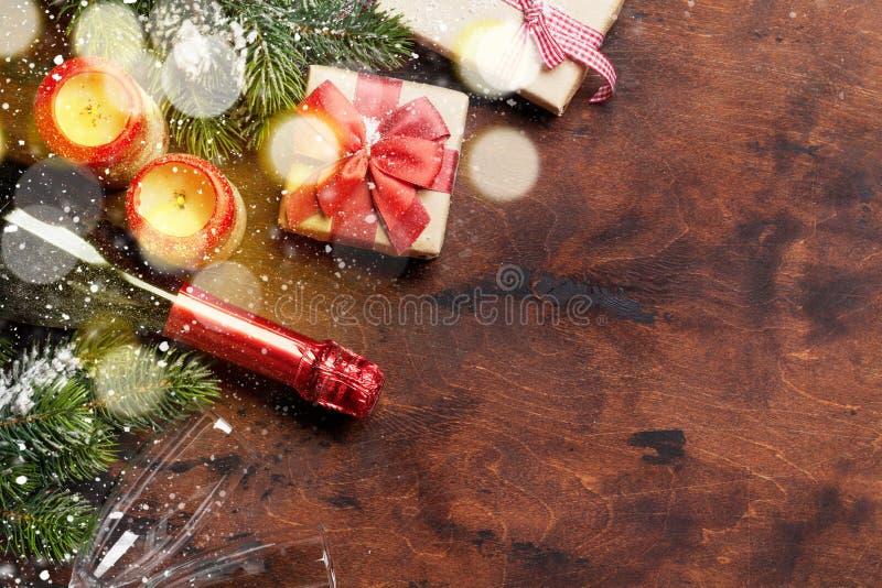 Caja de regalo de la Navidad, velas, champán y rama de árbol de abeto cubierta por la nieve en fondo de madera Contexto de Navida imagenes de archivo