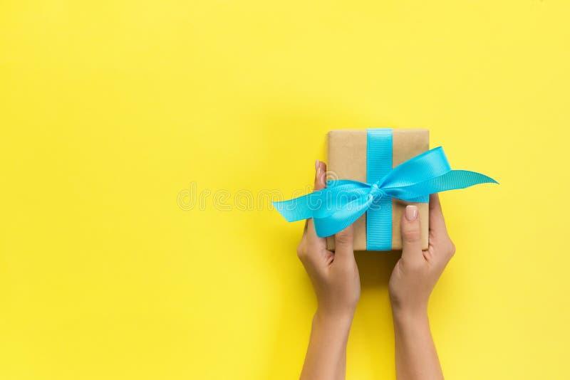 Caja de regalo de la tenencia de brazos de la mujer con la cinta azul en el fondo del color, visión superior foto de archivo libre de regalías